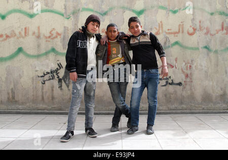 A group of boys outside the Elementary Girls' School No. 2 in the Irbid Palestinian refugee camp in northern Jordan - Stock Photo