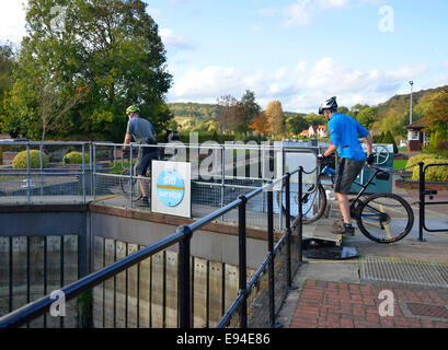 Two cyclists  on mountain bikes crossing Hambleden Lock gates on the River Thames, on the Oxfordshire/Buckinghamshire - Stock Photo