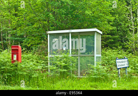 Post box and shabby little-used bus shelter surrounded by tall bracken and grass at road junction in woodland near - Stock Photo