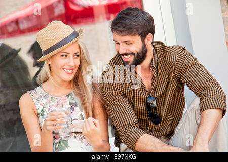 Happy young couple taking a break in town - Stock Photo