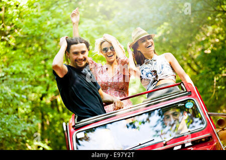 Young people in convertible car having fun - Stock Photo