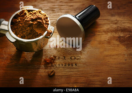 Freshly ground coffee beans in a metal filter on a wooden background with copyspace during preparation of a cup - Stock Photo