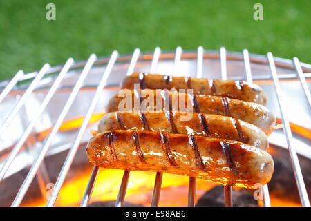 Row of beef and pork sausages sizzling on a hot barbecue over glowing coals while being cooked on a healthy outdoor - Stock Photo