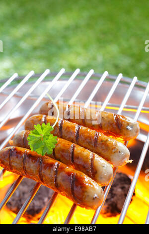 Delicious grilled sausages resting on the iron grid of a portable barbecue over glowing coals as they cook to perfection - Stock Photo