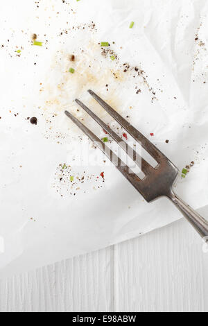Old kitchen fork resting on stained white paper with scattered remnants of seasoning and spices on a white wooden - Stock Photo
