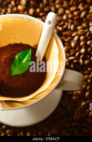 Fresh ground coffee and a green leaf in a portable filter funnel on a bed of whole roasted beans during preparation - Stock Photo