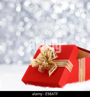 Colourful red Christmas gift decorated with a gold ribbon and bow in winter snow with a bokeh of falling snowflakes - Stock Photo