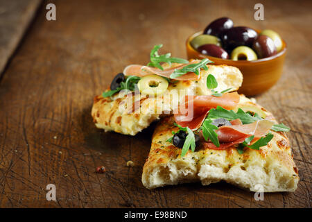 Ham and rocket on fresh Italian focaccia bread garnished with sliced olives lying on an old wooden kitchen table - Stock Photo