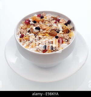 Bowl of delicious breakfast muesli with oat and wheat flakes mixed with dried fruit and nuts served in a white ceramic - Stock Photo