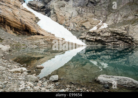 Edge of the Briksdal Glacier near Olden, Norway, reflecting in the lake below - Stock Photo