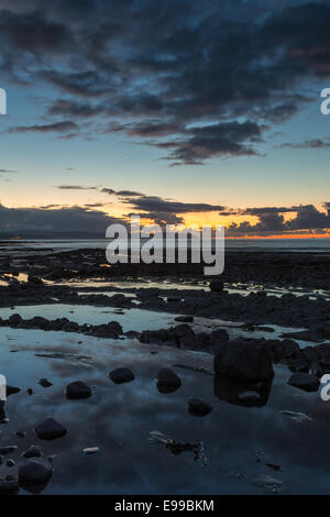 The sun sets at the end of an Autumn day over the Bristol Channel at Kilve - Stock Photo