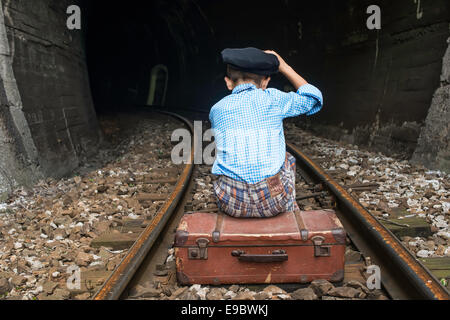 Child in vintage clothes sits on railway road in front of a tunnel. - Stock Photo