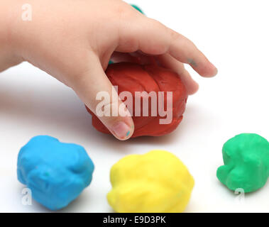 Child's hand take red plastic clay ball. White background. - Stock Photo