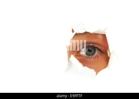 Girl looking through a hole in paper - Stock Photo