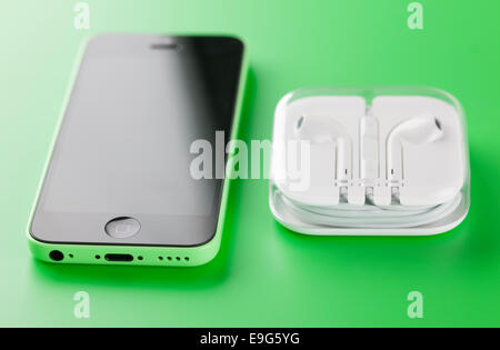 Tambov, Russian Federation - October 16, 2013 Apple iPhone 5C Green Color with new Apple EarPods in plastic box. - Stock Photo
