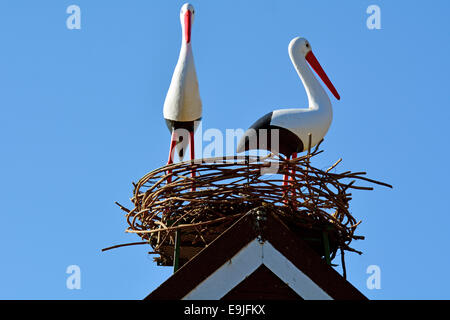 Two European white stork (Ciconia ciconia ciconia) with nest on a house roof. - Stock Photo