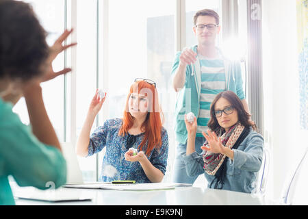 Angry businesspeople throwing paper balls on colleague in creative office - Stock Photo