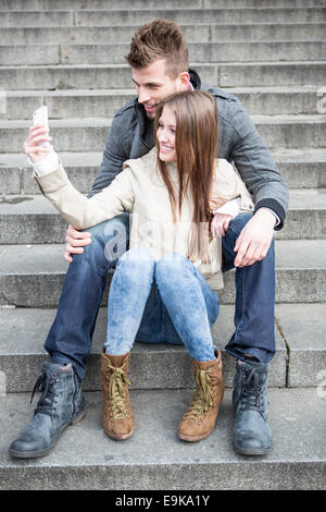 Full length of young couple taking picture of themselves while sitting on steps outdoors - Stock Photo