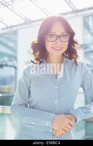 Portrait of smiling businesswoman leaning on railing in office - Stock Photo