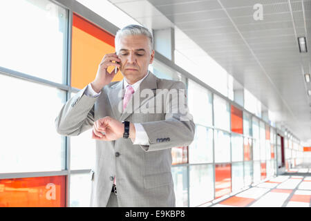 Middle aged businessman checking time while on call at railroad station - Stock Photo