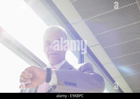 Middle aged businessman checking time at railroad station - Stock Photo