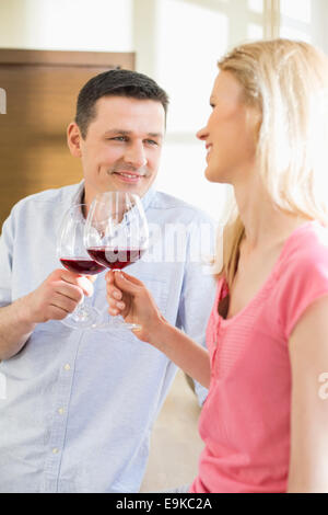 Happy couple toasting red wine glasses in kitchen - Stock Photo