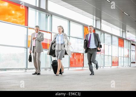 Full length of businesspeople rushing in railroad station - Stock Photo
