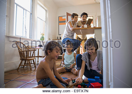 Children playing on kitchen floor - Stock Photo