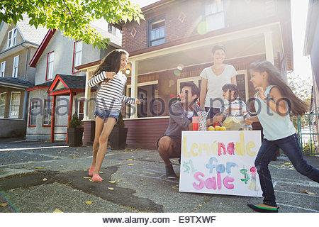 Family at lemonade stand on sidewalk outside house - Stock Photo