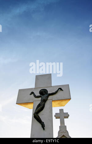 A stone statue of Jesus Christ crucified on cross at sunset. - Stock Photo