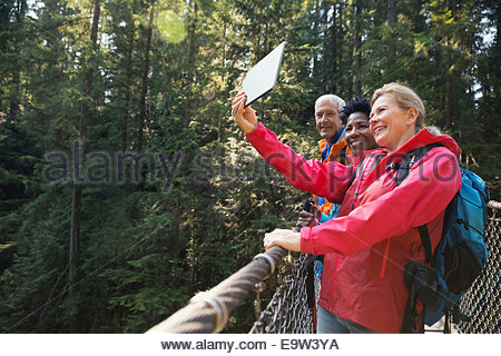 Friends taking selfie with digital tablet in woods - Stock Photo