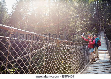 Friends taking selfie with digital tablet on footbridge - Stock Photo