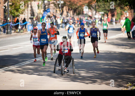 Runners, including a wheelchair participant, pass through Harlem in New York in the marathon - Stock Photo