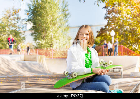 Smiling girl holds skateboard, sits in playground - Stock Photo