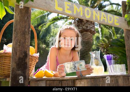Portrait of girl on lemonade stand holding up one hundred dollar bill - Stock Photo