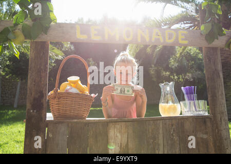 Portrait of girl on lemonade stand holding up one dollar bill - Stock Photo