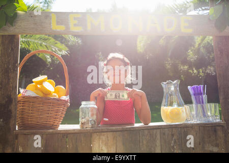 Portrait of proud girl on lemonade stand holding up one dollar bill - Stock Photo
