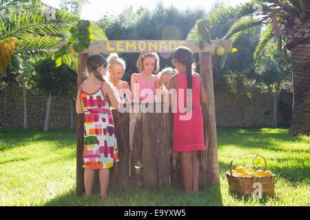 Five girls buying and selling fresh lemonade at lemonade stand in park - Stock Photo