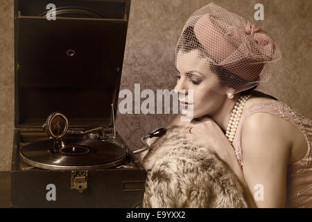 Vintage 1920s style lady in pink listening to an antique record player - Stock Photo