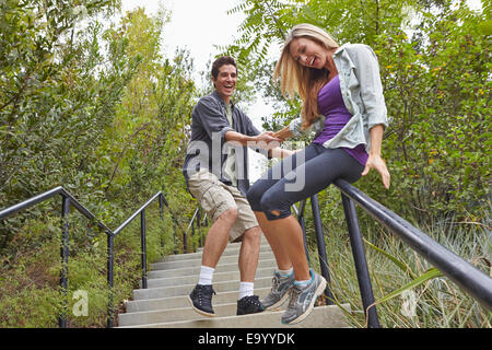 Couple sliding down step railing in forest - Stock Photo