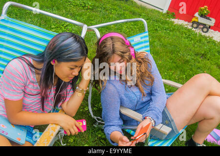 Girls listening to music together in garden - Stock Photo