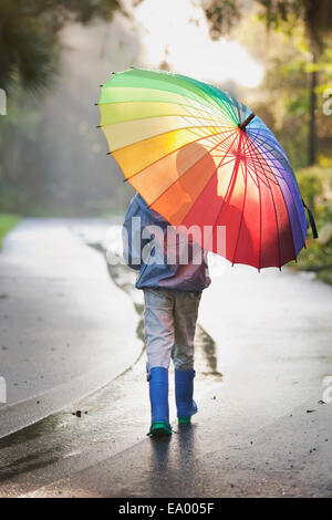Rear view of boy carrying umbrella on street - Stock Photo