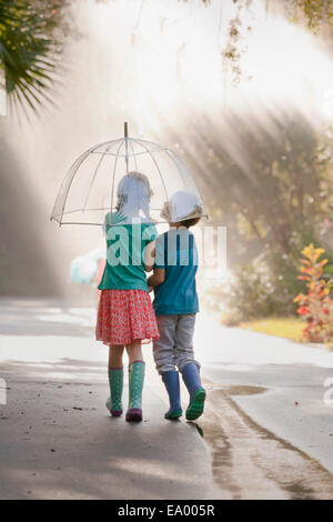 Rear view of boy and girl carrying umbrella on street - Stock Photo