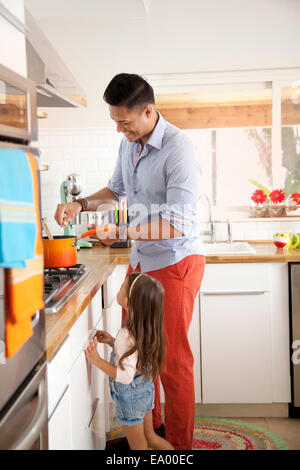 Father and daughter cooking in kitchen - Stock Photo