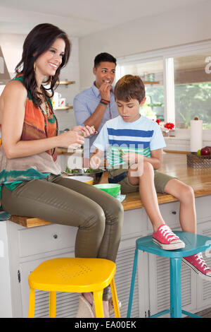 Boy sitting on kitchen counter with mother and father - Stock Photo