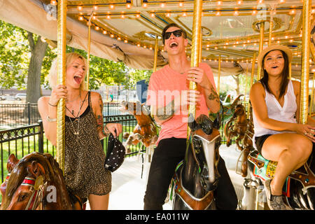Three young adult friends riding horse carousel in park - Stock Photo