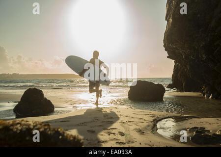 Mature man running towards sea, holding surf board - Stock Photo