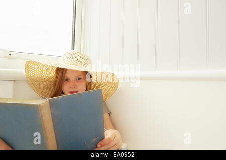 Girl in sunhat reading in holiday apartment porch - Stock Photo