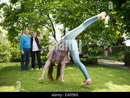 Grandparents and granddaughter doing acrobatics in garden - Stock Photo
