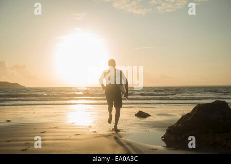 Mature man, running towards sea, holding surf board - Stock Photo